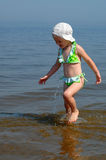The little girl suit goes on water. The little girl in a bathing suit goes on water Stock Photography