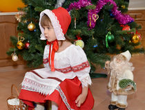The little girl in a suit of the Little Red Riding Hood and a figurine Santa Claus about a New Year tree Stock Images