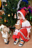 The little girl in a suit of the Little Red Riding Hood with toy Santa Claus about a New Year tree Stock Photography