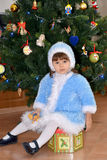 The little girl in a suit of the Snow Maiden sits about a New Year tree Stock Image