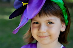 The little girl in a suit of violet flower is smiling on the bac Royalty Free Stock Photo
