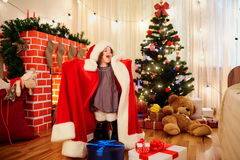 Little girl in a suit, wearing Santa Claus laughing, screaming, Stock Photos