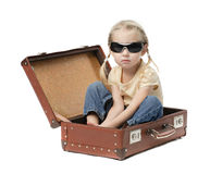 Little girl in suitcase. Cute little girl sitting in open suitcase isolated on white stock photos