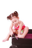 Little girl in a suitcase. Isolated on a white background Stock Image