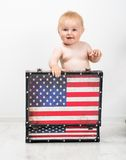Little girl with a suitcase. Baby with a suitcase in colors of American flag Stock Photo