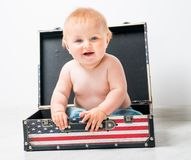 Little girl with a suitcase. Cute baby in a suitcase with American flag Stock Images