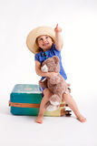 Little girl with a suitcase. Little cute girl sitting on a suitcase with a teddy bear ready to travel Royalty Free Stock Image
