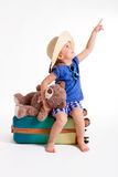 Little girl with a suitcase. Little cute girl sitting on a suitcase with a teddy bear ready to travel. It shows a side finger Stock Photo