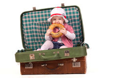 Little girl in the  suitcase eating  bread Royalty Free Stock Photos