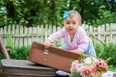 Little girl on suitcase Stock Images