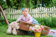 Little girl on suitcase Stock Image