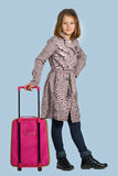 Little girl with a suitcase is preparing to travel Stock Photo