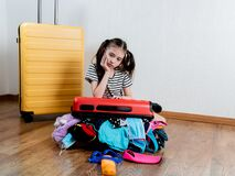 Little girl with suitcase ready for travel. Things spilled on the floor from the open suitcase.