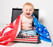Little girl with a suitcase. Smiling cute baby in a suitcase with American flag Royalty Free Stock Image
