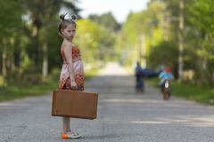 Little girl with suitcase standing on the road. Stock Images