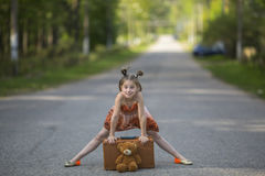 Little girl with a suitcase and teddy bear on the road. Stock Photos