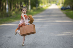 Little girl with suitcase and Teddy bear on the road. Walking. Royalty Free Stock Photos