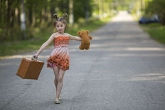 Little girl with suitcase and Teddy bear walking is on the road. Royalty Free Stock Image