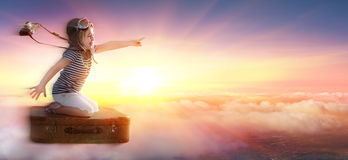 Little Girl On Suitcase In Trip Over Clouds. At Sunset Stock Images