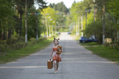 Little girl with suitcase walking along the road. Walking. Stock Photo