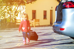 Little girl with suitcases travel by car, family tourism Royalty Free Stock Image