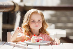 The little girl in a summer cafe Stock Image