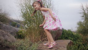 Little girl in a summer dress climbing a mountain of stones stock footage