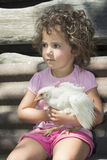 Little girl in the summer in the garden holding a chicken. Royalty Free Stock Photography