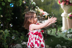 Little girl in summer garden. Playing with soap bu Stock Image