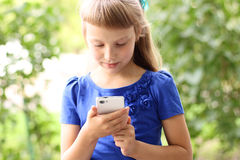 Little girl  summer park talking on the phone, in a blue dress. Blonde Royalty Free Stock Images