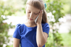 Little girl  summer park talking on the phone, in a blue dress. Blonde Stock Photo