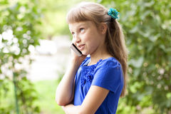 Little girl  summer park talking on the phone, in a blue dress. Blonde Royalty Free Stock Photos