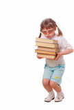Little girl in sun glasses carries a stack of book Royalty Free Stock Images