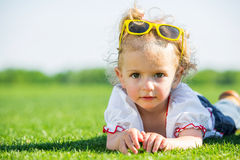 Little girl with sun glasses on a grass Royalty Free Stock Photo