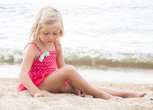Little Girl Sunbathing on the Beach Stock Photos