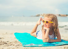 Little girl sunbathing on the beach. Royalty Free Stock Images