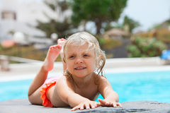 Little girl sunbathing near pool Stock Image