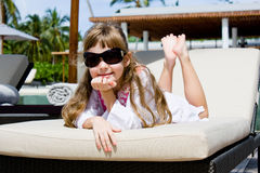 Little girl on sunbed. Little girl with sunglasses on sunbed in tropical resort Royalty Free Stock Photography