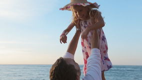 Little girl in sundress running along the sea to. Little happy girl in sundress running along the sea to father and he lifts her up in slow motion stock footage