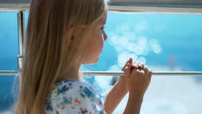 Little girl in sundress standing on an open balcony and looking at the sea Royalty Free Stock Images
