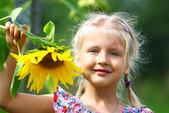 Little girl and sunflower Stock Image