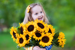Little girl with sunflowers Stock Image