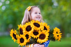 Little girl with sunflowers Stock Photos