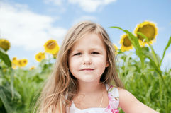 Little girl and sunflowers in a summer  day. Stock Image