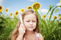 Little girl and sunflowers in a summer sunny day. Caring for your hair. Royalty Free Stock Photography