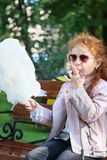 Little girl in sunglasses eats cotton candy. On bench in summer green park Royalty Free Stock Photos