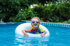 Little girl in sunglasses floating on the circle in the pool at a resort in the tropics. Pretty little girl swimming in outdoor pool and have a fun with Stock Images