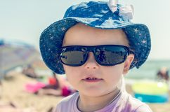Little girl in sunglasses and a hat on the sea in summer royalty free stock photography