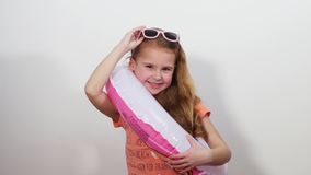 A little girl in sunglasses with a life ring invitingly winks at the camera stock video