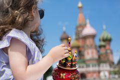 Little girl in sunglasses looking on Saint Basils Cathedral. With a miniature cathedral in hands royalty free stock images